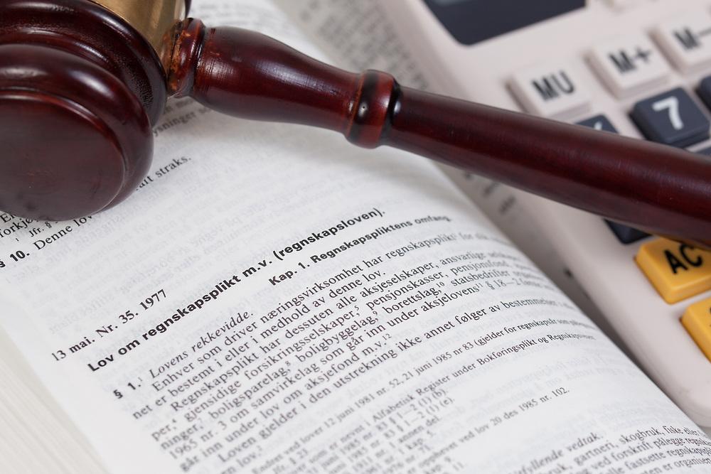 Fokus på innledningen til regnskapsloven i Norges lover. Kalkulator og dommerhammer er med på å understreke tematikken.