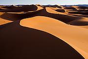 Sunset light strikes the large and expansive sand dunes of Erg Zehar, near M'hamid, Morocco.