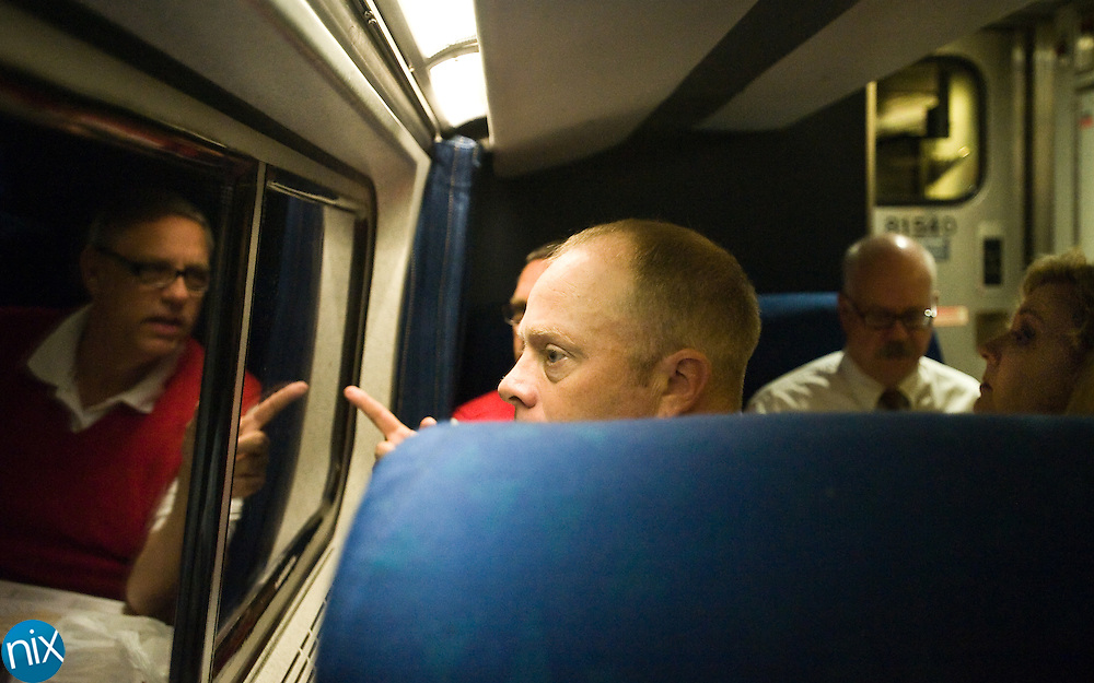 Harrisburg Town Councilmen Brian Leepard, at front, Phil Cowherd, at right, and Chuck Paxton, reflected, all of the Harrisburg N.C. Railroad Committee ride on the Carolinian, an Amtrak train, on their way to Raleigh to meet with the NCDOT about rail improvements in Harrisburg. (Photo by James Nix)