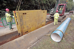Installing a new water main  A217 Burgh Heath, Surrey.<br /> Health and Safety use of Trench Box for shoring and cave in protection.