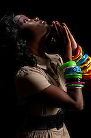 Young african american praying in dim light.