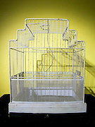 an empty metal wire birdcage against a yellow background