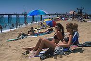 Young women in sunbathing on crowded sand beach at Balboa Pier, Newport Beach, Orange County, California