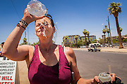 """20 JUNE 2012, PHOENIX, AZ:   A homeless woman provides water over her head in Phoenix, AZ, Wednesday. June 20 is the first day of summer in the northern hemisphere. The high temperature in Phoenix Wednesday soared to over 110 (F), well above the normal of 105. The hot weather is especially stressful on the homeless, who don't have the opportunity to get into air conditioning or access to cold water. """"I Will Listen,"""" an outreach organization that assists the homeless and community of street people in Phoenix, AZ, provides free food and cold drinks to the homeless in central Phoenix. They ran out of drinks and food in about one hour during Wednesday's outreach.      PHOTO BY JACK KURTZ"""