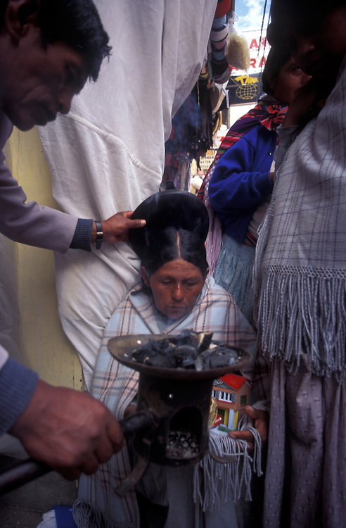 An indigenous woman has a dummy of her home ritually blessed for good fortune.Witch doctor's market, La Paz