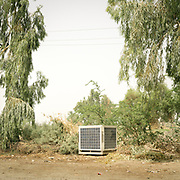 A solar panel cube used to pump water lies next to the road.