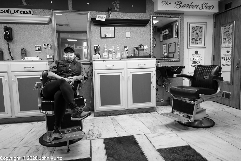 01 OCTOBER 2020 - DES MOINES, IOWA:  STEPHANIE MATTISON, a downtown barber, waits for customers in her shop in the skywalk. Mattison said she used to be busy all day, but when the pandemic struck in March her business dropped to next to nothing. Now she said she's lucky to see one or two customers a day. The economy in downtown Des Moines is still feeling the affects of the COVID-19 shutdown ordered in March. Seven months after the shutdown, employers still have their workers working from home. Restaurants, barbershops, and retail are feeling the impact. Many have closed or cut back on workers and hours.       PHOTO BY JACK KURTZ