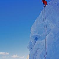 Sierra Nevada, California. Mountaineer rappels over glacier bergshrund crevasse on Palisade Glacier.