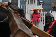 An rainy day onlooker watches a passing Via Crucis procession on W. Estes St.  in Chicago's Rogers Park neighborhood. The religious portrayal recounts the biblical steps of Jesus Christ being condemned to death, followed by his crucifixion and entombment.