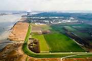 Nederland, Zeeland, Zeeuws-Vlaanderen, 01-04-2016; Hertogin Hedwige polder gezien naar de Belgische Prosperpolder, reeds ontpolderd. Westerschelde links, kerncentrale Doel aan de horizon. In verband met de verdieping van de vaargeul van de Westerschelde moet er volgens de Europese habitatrichtlijn natuurcompensatie komen. Door de polders te ontpolderen wordt er grond terug gegeven aan de natuur, zogenaamde natuurcompensatie. <br />