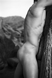 detail of a nude man leaning against a rock formation in Death Valley National Park