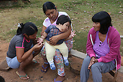 Surui families looking after their children. Cleaning insect bites.<br /><br />An Amazonian tribal chief Almir Narayamogo, leader of 1350 Surui Indians in Rondônia, near Cacaol, Brazil, with a $100,000 bounty on his head, is fighting for the survival of his people and their forest, and using the world's modern hi-tech tools; computers, smartphones, Google Earth and digital forestry surveillance. So far their fight has been very effective, leading to a most promising and novel result. In 2013, Almir Narayamogo, led his people to be the first and unique indigenous tribe in the world to manage their own REDD+ carbon project and sell carbon credits to the industrial world. By marketing the CO2 capacity of 250 000 hectares of their virgin forest, the forty year old Surui, has ensured the preservation, as well as a future of his community. <br /><br />In 2009, the four clans and 25 Surui villages voted in favour of a total moratorium on logging and the carbon credits project. <br /><br />They still face deforestation problems, such as illegal logging, and gold mining which causes pollution of their river systems