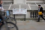 Blurred pedestrian and cyclists pass the street sign on a Westminster pavement, where Parliament Street becomes Whitehall, the centre for government buildings.