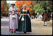 Two colonial Virginian ladies in dresses walk main street of 18th-c. Colonial Williamsburg. Virginia