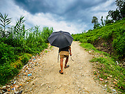 04 AUGUST 2015 - KHOKANA, NEPAL:  A farmer walks up a dirt road in Khokana, Nepal. He had been working in his rice fields.       PHOTO BY JACK KURTZ