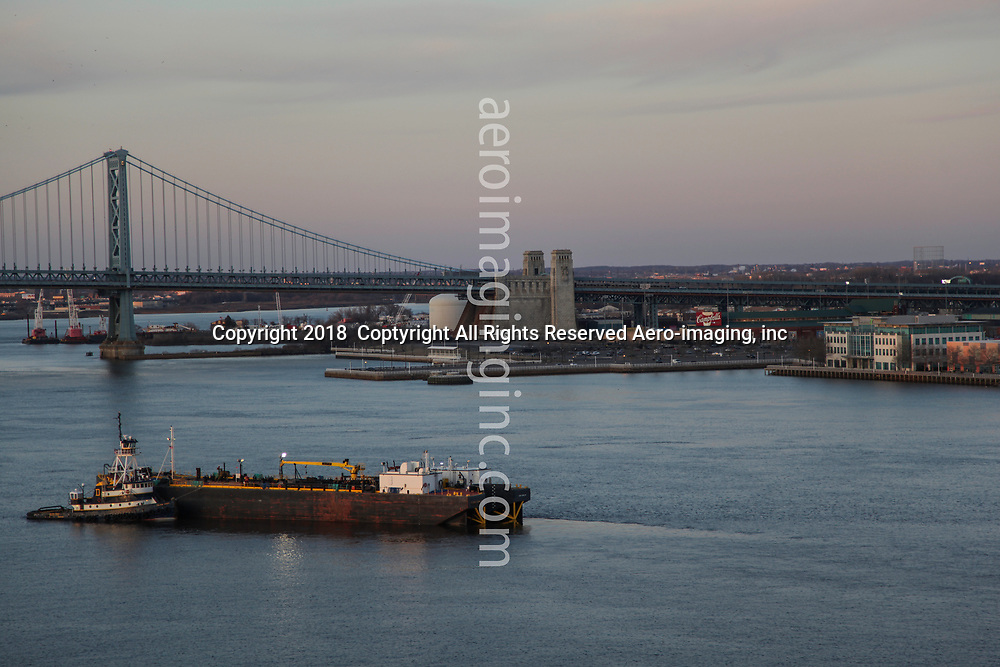 Aerial view of ATB and Tugboat in the Delawware River wwith the Ben Franklin Bridge and Camden Waterfront