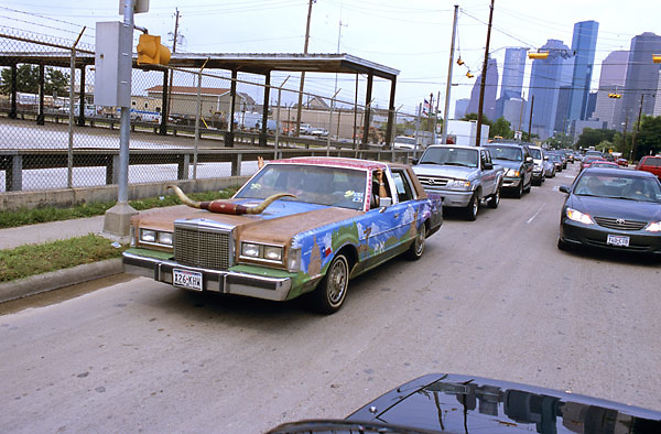 Stock photo of an art car with longhorns on the front driving through traffic