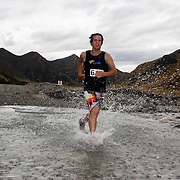 Runner Matthijs Groeneveld crosses Moke Creek on the Ben Lomond High Country Station during the Pure South Shotover Moonlight Mountain Marathon and trail runs. Moke Lake, Queenstown, New Zealand. 4th February 2012. Photo Tim Clayton