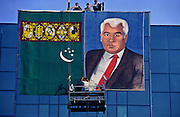 Ashgabat, Turkmenistan, October 1997..Workers raise a portrait of President Saparmurat Niyazov on a city centre department store. Poverty-stricken, but rich in oil and gas resources, this Central Asian former Soviet republic is ruled by the autocratic President Saparmurat Niyazov, or Turkmenbashi as he has renamed himself...............Hollandse Hoogte