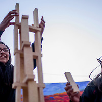 Shannon Begay, left, and Shantel Slivers work together to build a tower out of wooden blocks during ArtsCrawl in downtown Gallup Saturday.