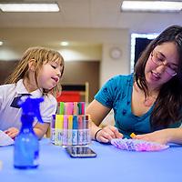 031815       Cable Hoover<br /> <br /> Riley Plese peeks over at work of her mother, Rachel Chavez, as the pair color coffee filters to make paper flowers Wednesday at Octavia Fellin Public Library Children's Branch in Gallup.