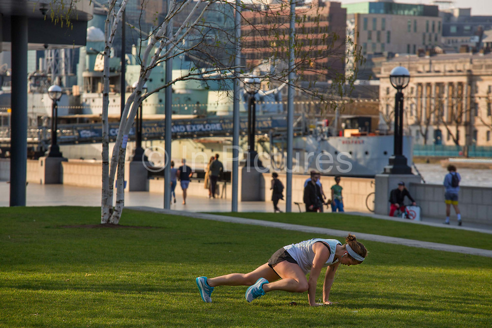 Keeping fit during the lockdown by Tower Bridge at 5pm on 9th April 2020 in London, United Kingdom. Normally crowded with people leaving work the City of London is like a ghost town as workers stay home during the Coronavirus pandemic.