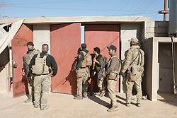 Licensed to London News Pictures. 20/02/2017. Albu Saif, Iraq. Iraqi soldiers of the Iraqi Emergency Response Division gather in the gateway of a home as Iraqi Security Forces assault the village of Albu Saif during the offensive to retake western Mosul from Islamic State forces.<br /> <br /> The settlement of Albu Saif is located on high ground overlooking Mosul Airport and as such is a strategic point that needs to be taken as part of the operation to retake the western side of Mosul. Photo credit: Matt Cetti-Roberts/LNP