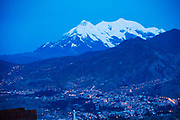 La Paz at night with snow capped Mount Illimani in the background.