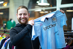 © Licensed to London News Pictures . 29/10/2018. Manchester , UK . KEN FITKIN (30) with the newly signed Manchester City shirt that he wore when he was six . Former Manchester City footballer Georgi Kinkladze attends a shirt and poster signing at the Classic Football Shirts shop in Barton Arcade in Manchester City Centre . Photo credit : Joel Goodman/LNP