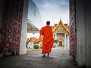 "21 JULY 2013 - BANGKOK, THAILAND:   A Buddhist monk walks into Wat Benchamabophit on the first day of Vassa, the three-month annual retreat observed by Theravada monks and nuns. On the first day of Vassa (or Buddhist Lent) many Buddhists visit their temples to ""make merit."" During Vassa, monks and nuns remain inside monasteries and temple grounds, devoting their time to intensive meditation and study. Laypeople support the monastic sangha by bringing food, candles and other offerings to temples. Laypeople also often observe Vassa by giving up something, such as smoking or eating meat. For this reason, westerners sometimes call Vassa the ""Buddhist Lent.""      PHOTO BY JACK KURTZ"