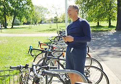 Mature Man in Park Listening to Music on Smartphone