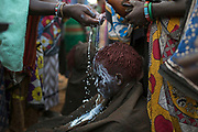 A Pokot girl is smeared with a natural white paint by other women as part of the ceremony after having being circumcised, about 80 kilometres from the town of Marigat in Baringo County, Kenya, October 17, 2014. The circumcision is done by an elder of the community. The ceremony starts the evening before the girls get circumcised and involves women and elders of the community gathering together, singing and dancing through out the night in encouragement to the girls who together wait inside a hut for first light. The traditional practice of circumcision within the Pokot is a right of passage that marks the transition to womanhood and a requirement to marriage within the community.