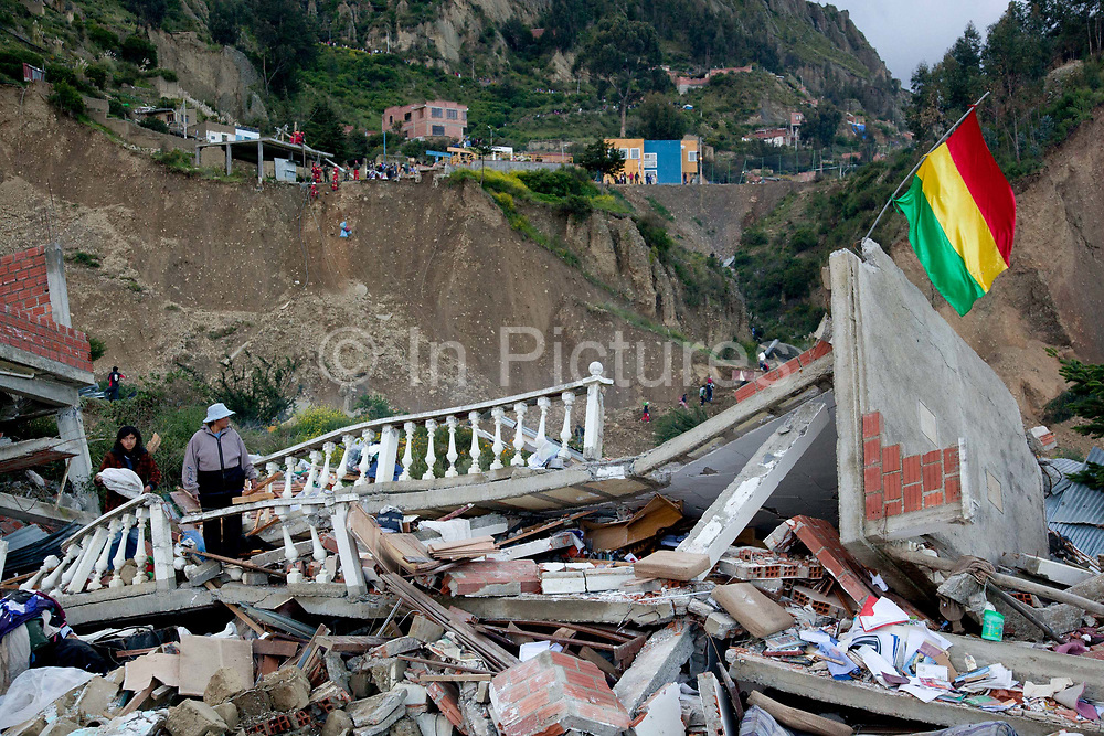Two women search for their belongings whilst a Bolivian flag flies amid ruined houses and rubble, after a major lansdlide in La Paz in 2011 made around 25,000 people homeless, due to heavy rain and poor infrastructure, there were no fatalities and only minor injuries sustained.