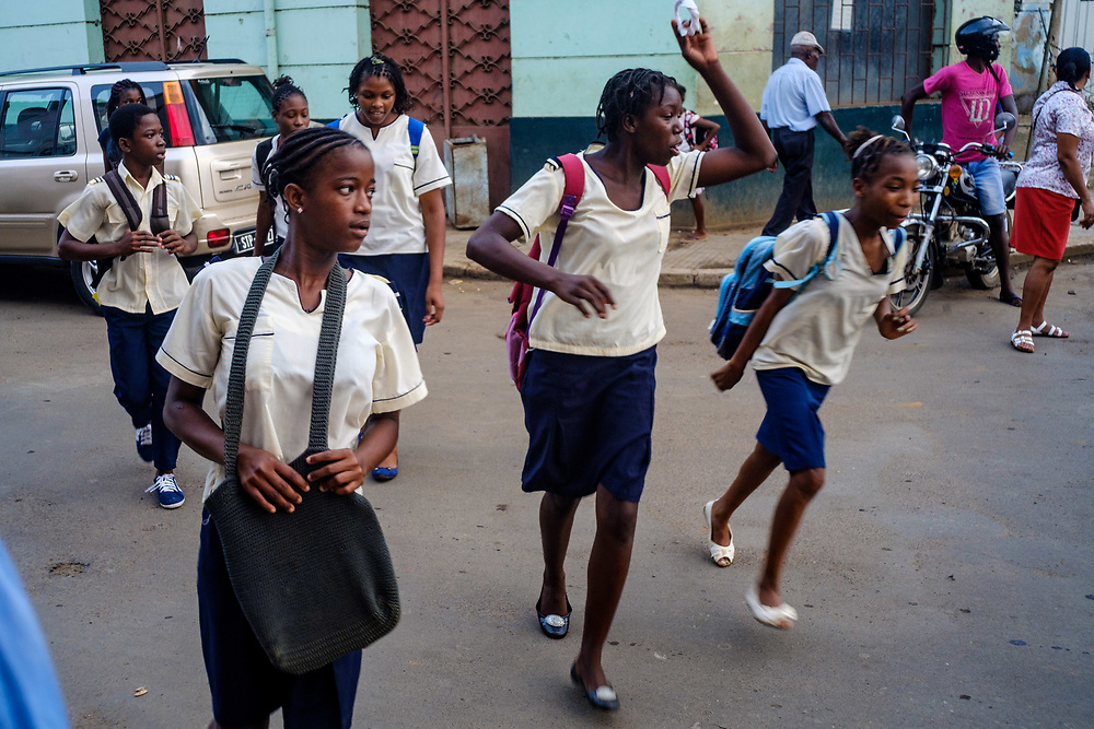 Young female students in colleage uniforms playing in São Tomé streets.