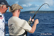 """fishing mate Walter """"Rooster"""" Morehead gives advice while angler Jon Givens brings in line while fishing on Reel Addiction, Vava'u, Kingdom of Tonga, South Pacific"""