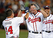 ATLANTA - JUNE 30:  Third baseman Chipper Jones #10 of the Atlanta Braves (center) congratulates teammate second baseman Martin Prado #14 after his game winning hit in the bottom of the 10th while Tim Hudson (right) looks on after the game against the Philadelphia Phillies at Turner Field on June 30, 2009 in Atlanta, Georgia.  The Braves beat the Phillies 5-4 in 10 innings.  (Photo by Mike Zarrilli/Getty Images)