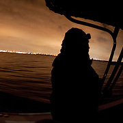 """Mark Allen White, Supervisory Marine Interdiction Agent with Customs and Border Protection, .San Diego Air & Marine Branch, patrols the waters near the US/Mexico border for undocumented immigrants in the early morning hours. The unit is also on patrol for gun smugglers hauling firearms into Mexico which is helping to fuel the Narco wars raging in Mexico. For more images, search for """"immigration by air and sea"""". Please contact Todd Bigelow directly with your licensing requests."""