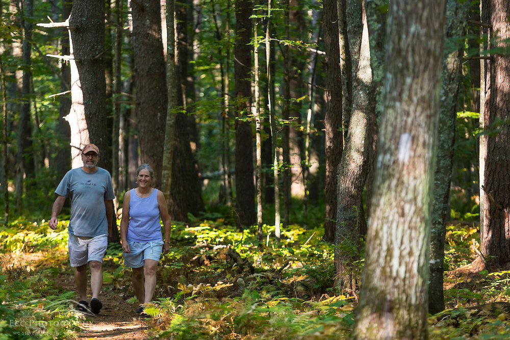 A man and a woman walk a forest trail at the Smelt Brook Preserve in York, Maine.