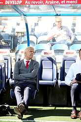 Arsenal manager Arsene Wenger sits in the dug out below a sign saying Au revior, Arsene, et merci