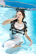 A young woman in white dress floats underwater Model release available