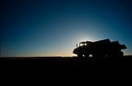 """Iron ore haulage trucks wait on the """"go-line"""" waiting for start of a shift at a mine site in the Pilbara region of Western Australian."""