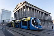 Tram passing Town Hall in the City Centre on 26th November 2020 in Birmingham, United Kingdom. The Midland Metro is a light-rail tram line in the county of West Midlands, England, operating between the cities of Birmingham and Wolverhampton via the towns of West Bromwich and Wednesbury. The line operates on streets in urban areas, and reopened conventional rail tracks that link the towns and cities. The owners are Transport for West Midlands with operation by National Express Midland Metro, a subsidiary of National Express.
