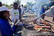 Namibians gather for their favorite snack, kapana (strips of freshly butchered beef) at the busy Oshetu Market near the Katutura area of Windhoek, Namibia. Vendors grill the popular snack over wood fires and serve it up by the handful in a piece of newspaper for about $0.50 (USD).