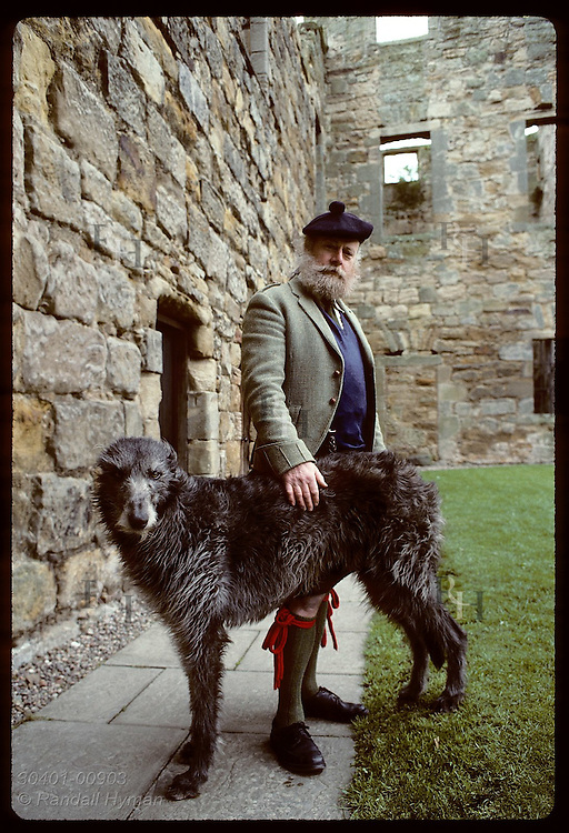 Raymond Morris, 30th Laird of Balgonie Castle, with deerhound in courtyard of 14th-cen home; Fife Scotland