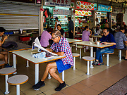 "11 DECEMBER 2018 - SINGAPORE:  A man reads his newspaper in a ""hawker"" court at the Haig Road Market and Food Centre in the Geylang neighborhood. The Geylang area of Singapore, between the Central Business District and Changi Airport, was originally coconut plantations and Malay villages. During Singapore's boom the coconut plantations and other farms were pushed out and now the area is a working class community of Malay, Indian and Chinese people. In the 2000s, developers started gentrifying Geylang and new housing estate developments were built.     PHOTO BY JACK KURTZ"