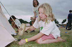 Children putting up tent in campsite using mallets and pegs during environmental awareness camp,