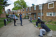 A young boy, with family and friends, plays with a toy parachute outside his home in Cressingham Gardens on 25th May 2016 in South London, United Kingdom. Cressingham Gardens is a council garden estate, located on the southern edge of Brockwell Park. It comprises of 306 dwellings and built to the design of Lambeth Borough Council architect Edward Hollamby in the early 1970s. In 2012, Lambeth Council proposed regeneration of the estate, a decision highly opposed by many residents. Since the announcement, the highly motivated campaign group Save Cressingham Gardens has been active.