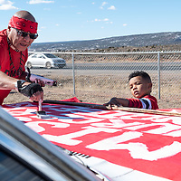 Damon Smith, left, and his helper Santana Motley, 5, put the finishing touches on the sign that will be carried during the Missing and Murdered Indigenous Women and Girls Walk in Ft. Defiance Friday.