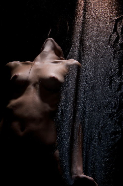 Young caucasian woman posing nude in dim light behind  translucent courtain.