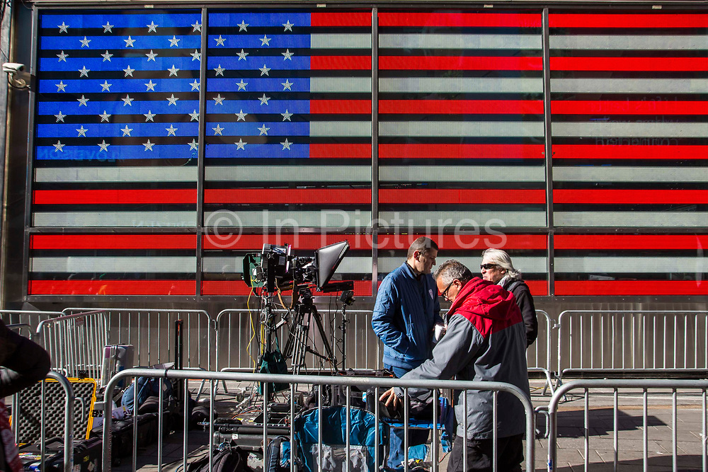 Media people setting up camera equipment in a designated area ring fences with crowd control barriers, in front of a large digital Flag of the United States on the side of the US Armed Forces Recruiting Station in Times Square, Midtown Manhattan, New York City, New York, United States.